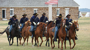 African American men in 19th century US Army uniforms on horseback.