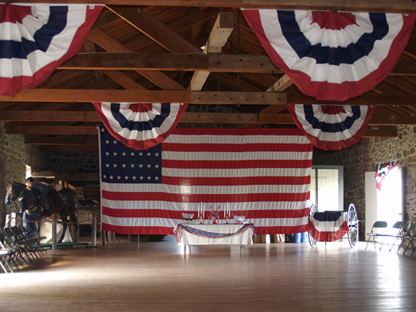 Historic warehouse with bunting and large flag hanging from rafters.