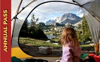 Young girl looking out of a tent door at a mountain range.