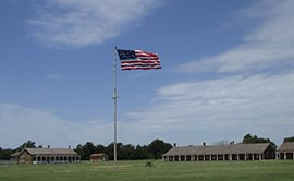 U.S. flag on tall flag pole.  Two sandstone buildings in background on either side of flagpole.