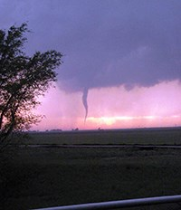 Evening view of prairie landscape with a tornado in the distance.