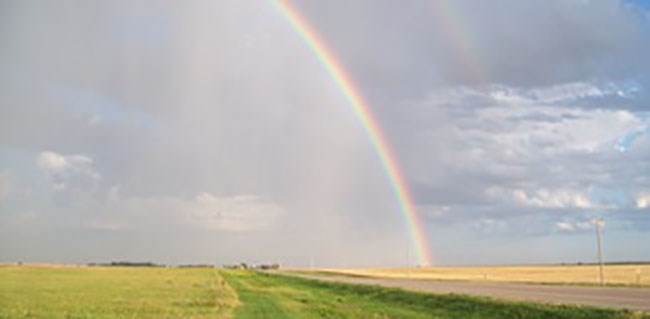 Rainbow over rural Kansas road.