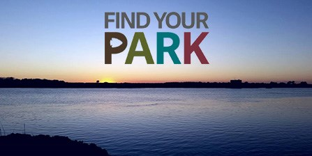 Sun setting behind Rattlesnake Island with the Find Your Park logo suspended in the sky