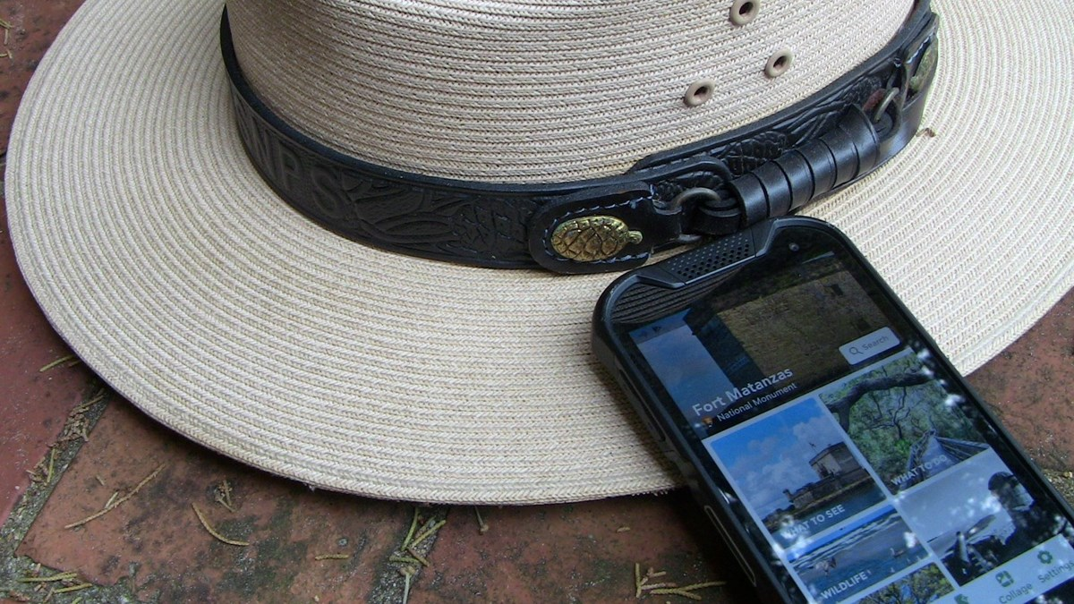 Ranger hat sitting next to phone with park app on screen.