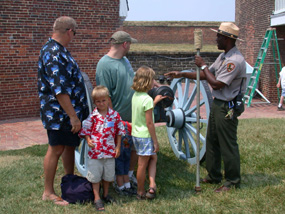 A Park Ranger gives an artillery talk to a few visitors.