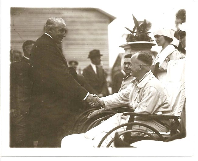 A black and white image of Warren G. Harding shaking hands with a soldier in a wheelchair.