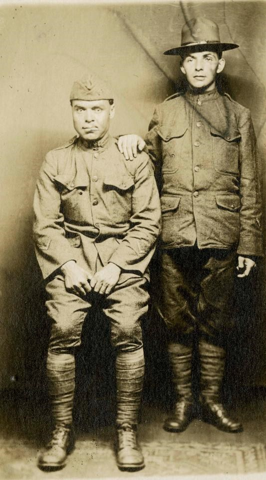 A black and white photograph of two World War I soldiers, one sitting and one standing. Each has a distorted face from needing facial reconstruction surgeries.