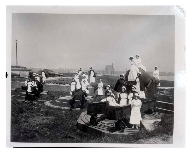 A black and white photograph of nurses sitting on the large rodman cannons around Fort McHenry.