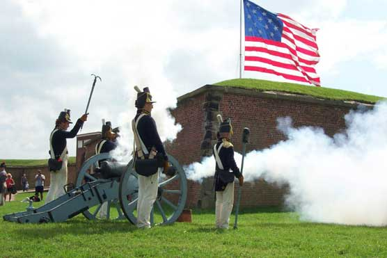 The Fort McHenry Guard fires a cannon as the Garrison Flag flies over the fort.