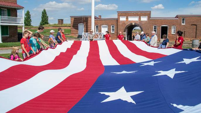 Visitors hold the edges of the 30-by-42 foot Star-Spangled Banner replica flag