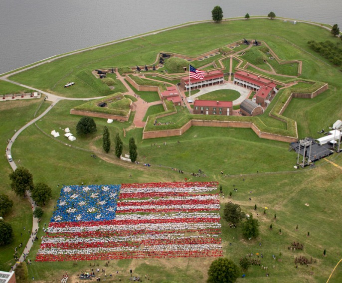 Aerial view of thousands of students creating a living flag on the lawn in front of the historic star fort