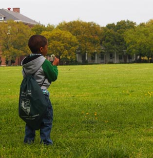 A young junior ranger examining a dandelion on the Parade Ground.
