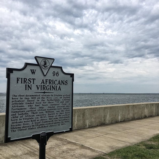 A sign explains how the first Africans in arrived Virginia. It stands along a sidewalk next to the water.