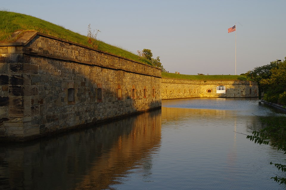 A view of the outside two stone bastion walls, a water moat, and a flagpole with the American flag flying against a blue sky.
