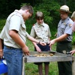 Three boy scouts and a prak ranger screening soil