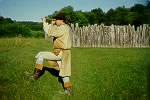 Re-enactor looking through spyglass outside Fort Necessity