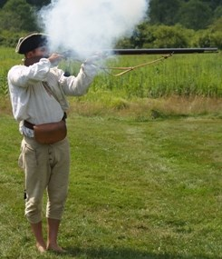 Re-enactor firing a flintlock musket