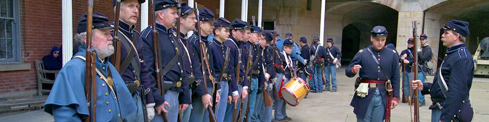 Line of Civil War re-enactors in uniforms with guns at Fort Point