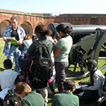 teacher and students gathered around cannon