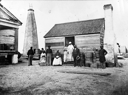 Family in front of cabin, Cockspur Island