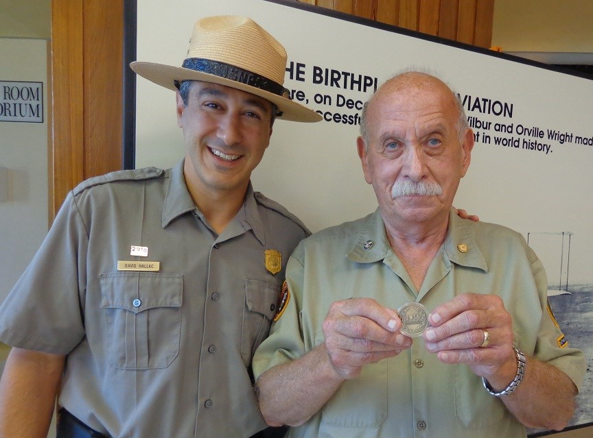Long-term Wright Brother National Memorial volunteer, Fred Hattman, receives the Centennial Volunteer Challenge Coin from Superintendent David Hallac