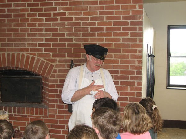 Volunteer portraying baker in education program