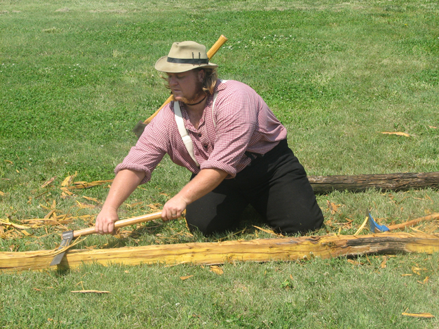 Reenactor Hewing a Log