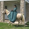 Lady riding sidesaddle on horseback