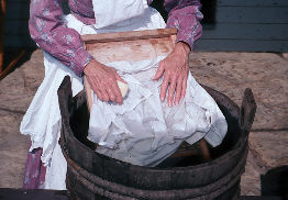 Laundress plunging hands into water
