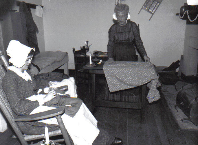 Two laundresses mend clothing in laundress quarters