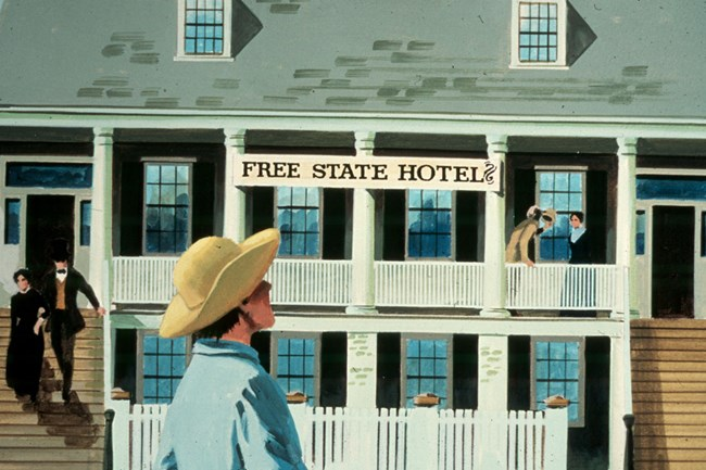 two story building with people gathered around with sign that says Free State Hotel