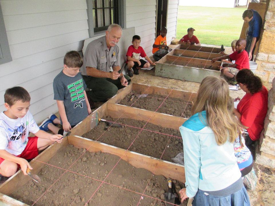 Youth led by an NPS employee gather around a wooden box full of dirt.  A mock archaeological dig is taking place.