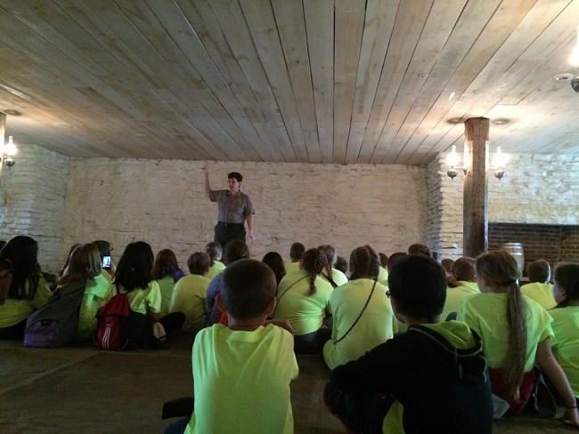 Groups of students wearing neon green shirts siting on a stone floor listening to a Park Ranger.