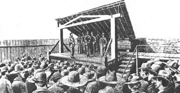 drawing of execution of Cherokee Bill showing large crowd gathered around gallows structure.  Cherokee Bill is standing on scaffold with a rope hanging from the cross beam.  Standing in the distance on the scaffold is a woman, Cherokee Bill's mother.