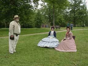 two women dressed in Civil War era dresses talk to a man dressed as a Confederate soldier