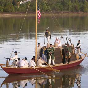 reconstructed keelboat on the Arkansas River with people dressed as soldiers from 1817