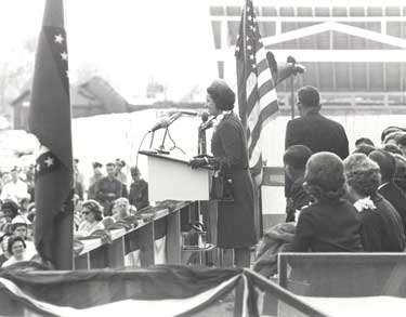 black and white photo showing Ladybird Johnson at podium during dedication of park.  American flag is behind her.
