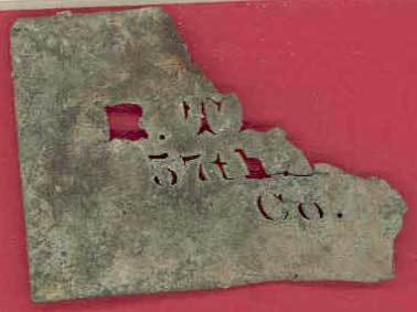 thin, corroded piece of metal with small cut-out letters and numbers.  R.T. 57th Co.