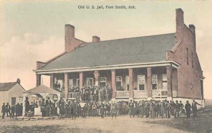 sepia postcard of people standing on grounds of old jail building