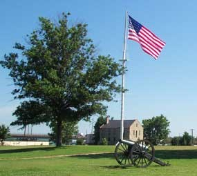 Garrison flag flies in middle of parade ground with commissary in distance