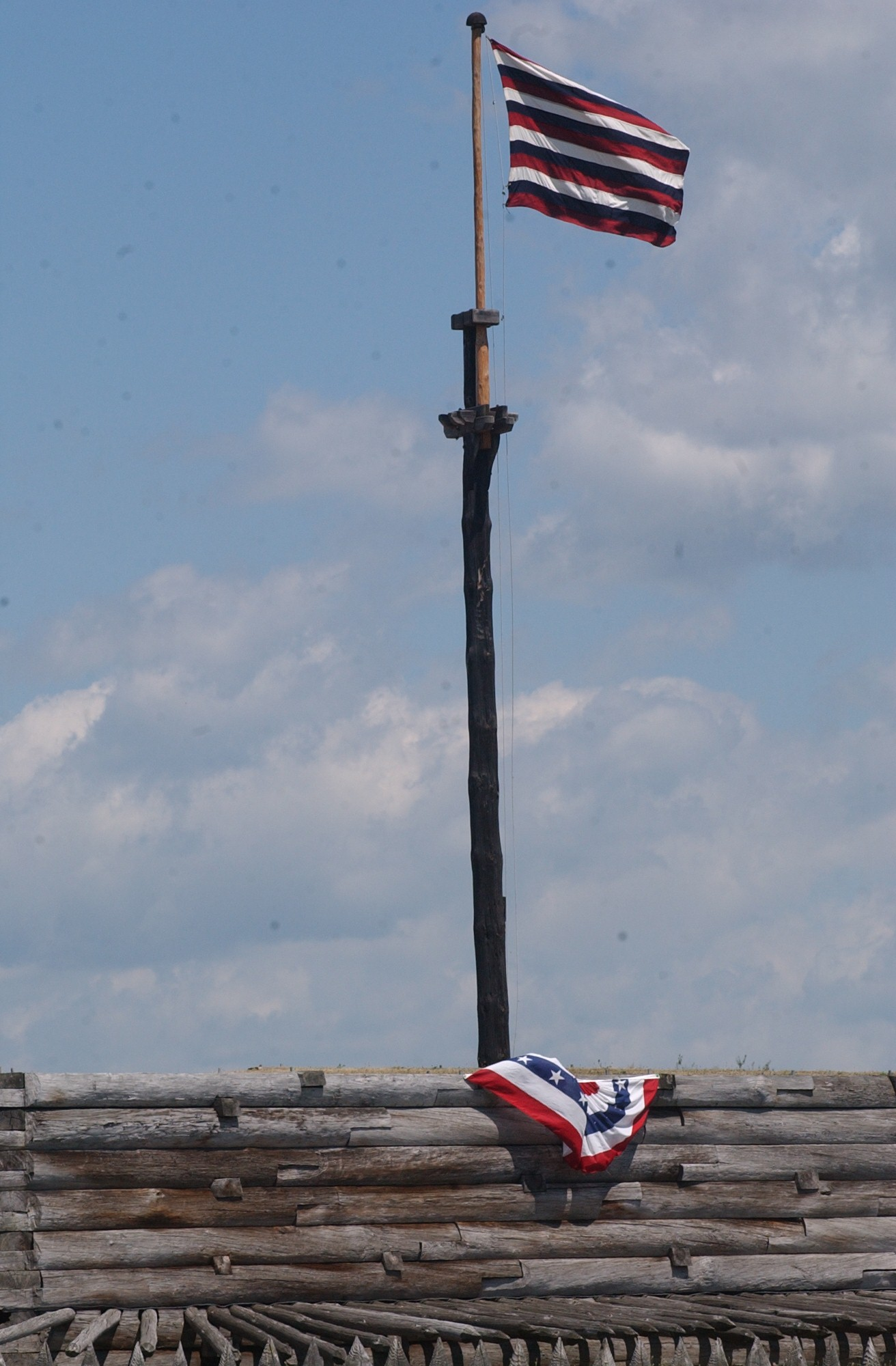 an alternating 13 stirped red, white, and blue striped flag flies in the sunlight over the fort wall