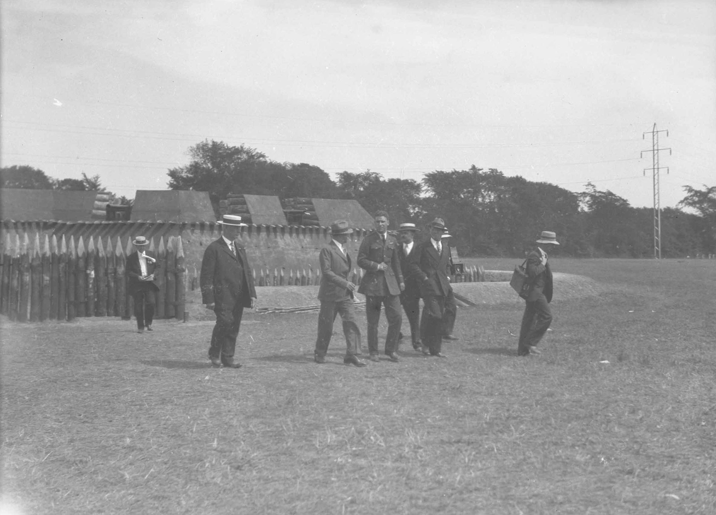 men in business suits walk in front of a tiny delicate looking fort with pickets and a ditch in the middle of a field