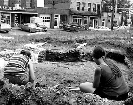 Two archeologists sit and dig during the 1970s excavations.
