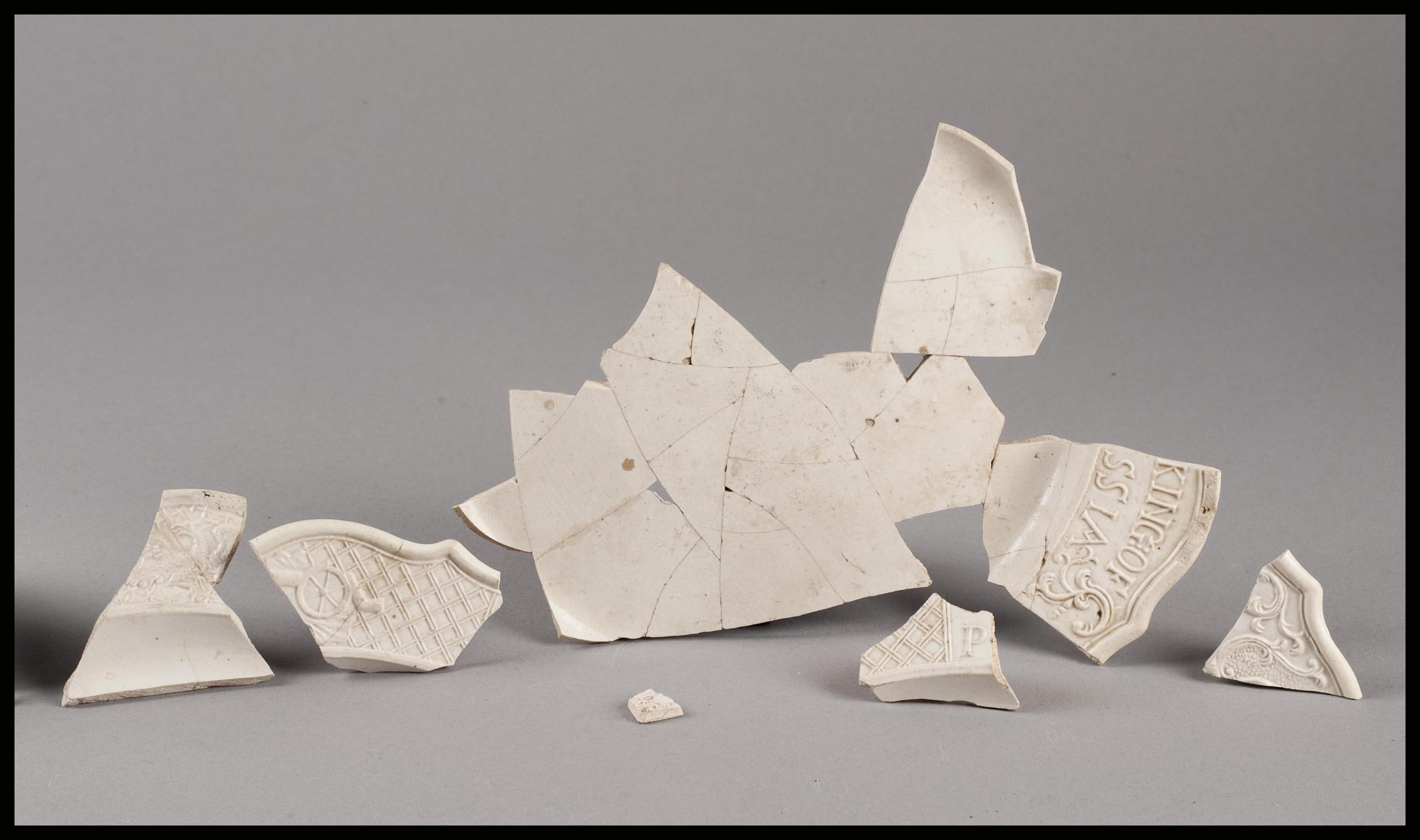Broken fragments of a plate are glued together, but the plate is not complete.
