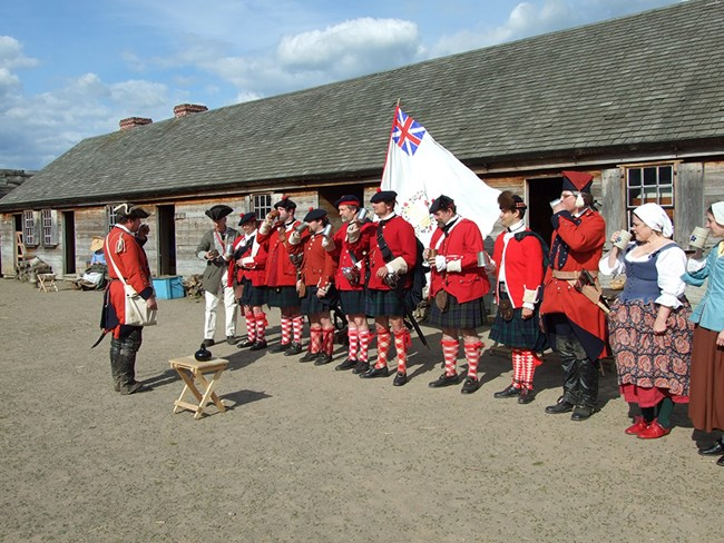 Men in bright red kilts stand shoulder to shoulder with cups in their hands.