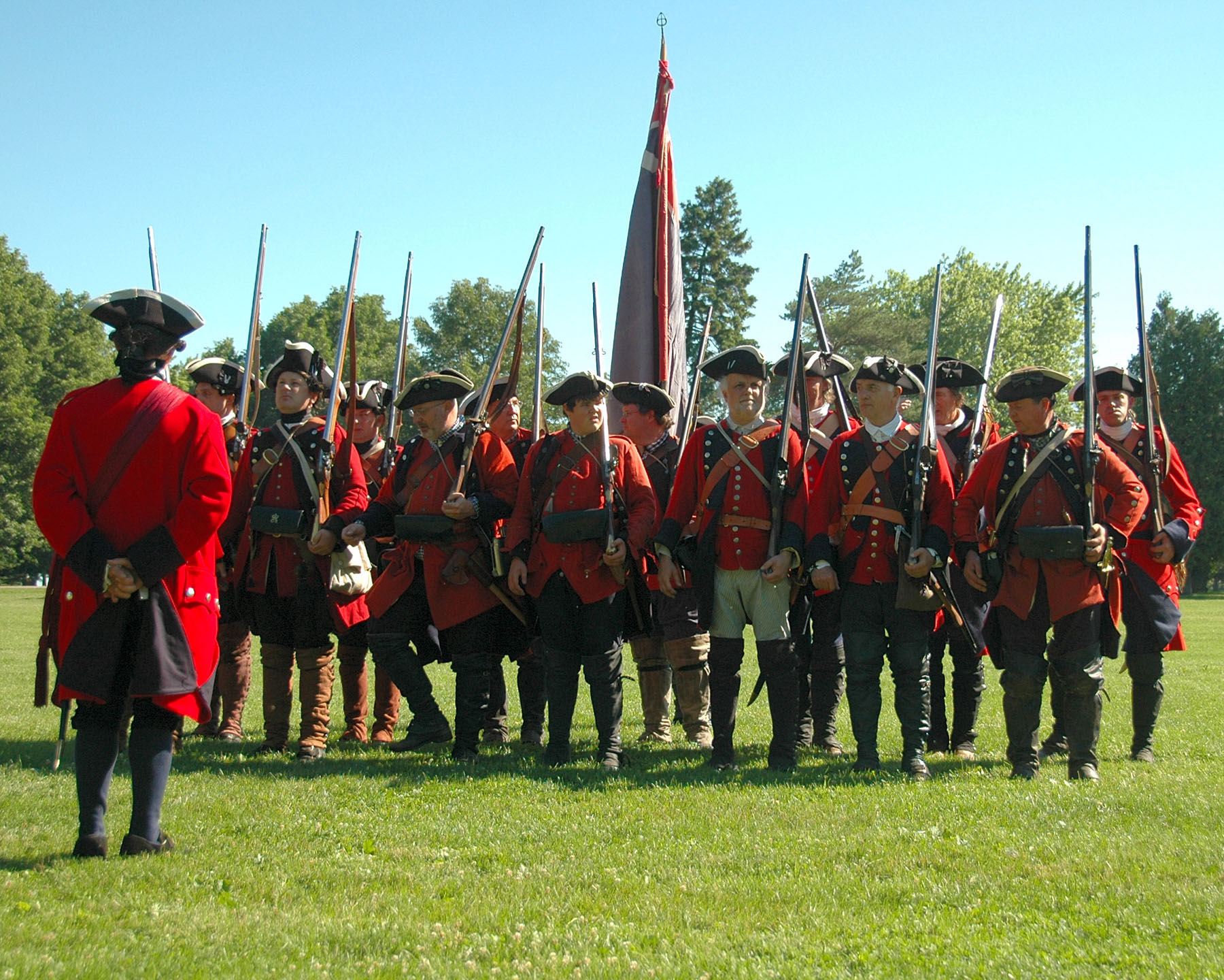 men in red jackets stand in a line with muskets.