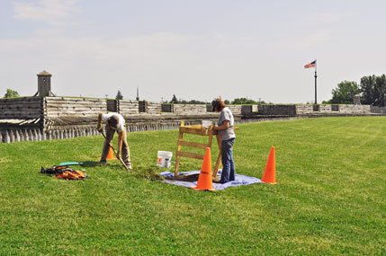Archeologists dig outside the reconstructed fort