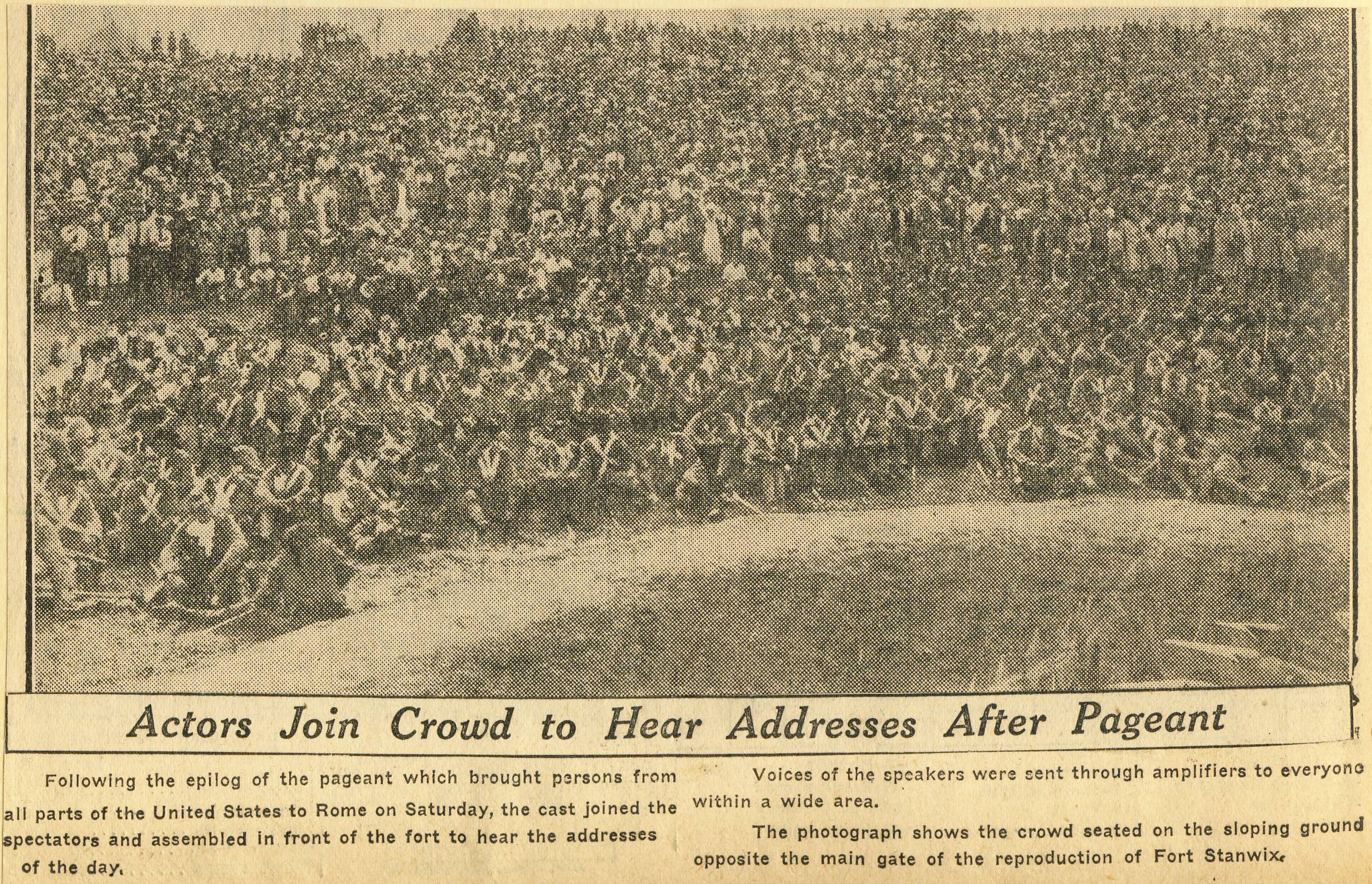 faded newsprint picture, of hundreds of people, in a crowd, peering at a miniature fort while a performance is enacted around it