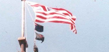 a flag with the British Union Jack in the corner and 13 red and white stripes alternating flutter rapidly in the breeze