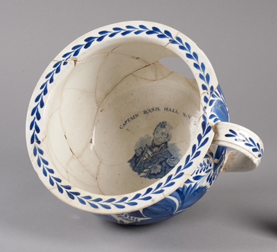 a nicely decorated large tea cup-like object has a handsome man's face at the bottom...this is a 19th century toilet!